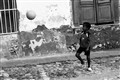 A kid playing soccer in Trinidad