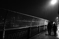 Walking across the bridge on a rainy night