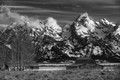 Black and white image of the Tetons with old buildings in the foreground.