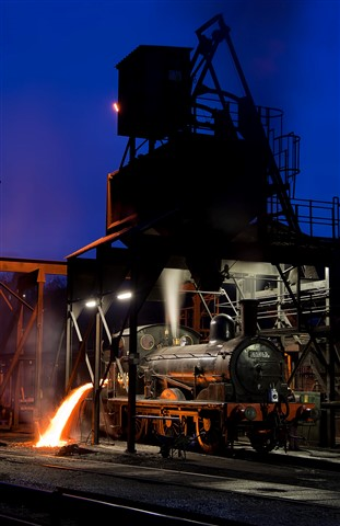 Four elements together - Throwing the fire from a steam locomotive under coaling stage at Grosmont, North Yorkshire, England