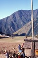 "Sherpas watching a Twin Otter depart Lukla, Nepal, below a prayer flag ""wind-sock"""
