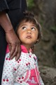 Taken in Wengding, a Wa village in Yunnan, China in 2015. The little girl's eyes caught my attention. I took the shot by lowering as much as I could so as to focus on the girl's eyes.