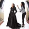 Designer helping her client wearing the Gown she made for her during a photoshoot