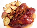 Photo of baked barbecue chicken served with potatoes.