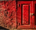 A little red door with matching wall color.