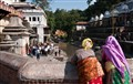 A view from a bridge as seen by two women in Pashupatinath Temple, Kathmandu