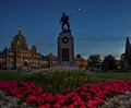 A statue is of a soldier is silhouetted against the blue sky with the crescent moon.  Location Victoria, Vancouver Island, Canada