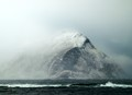 Fog shrouded rocky island emerging from the North Sea near Bergen Norway.