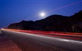 Truck light trails under fullmoon